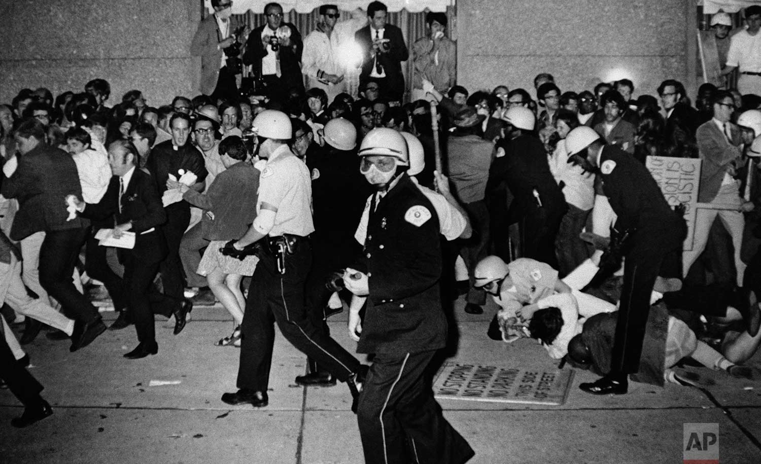 Jeers greet Chicago Police Aug. 29, 1968 as they attempt to disperse demonstrators outside the Conrad Hilton, Democratic National Convention headquarters in Chicago. Some police struggle with several demonstrators on the sidewalk. (AP Photo/Michael Boyer)