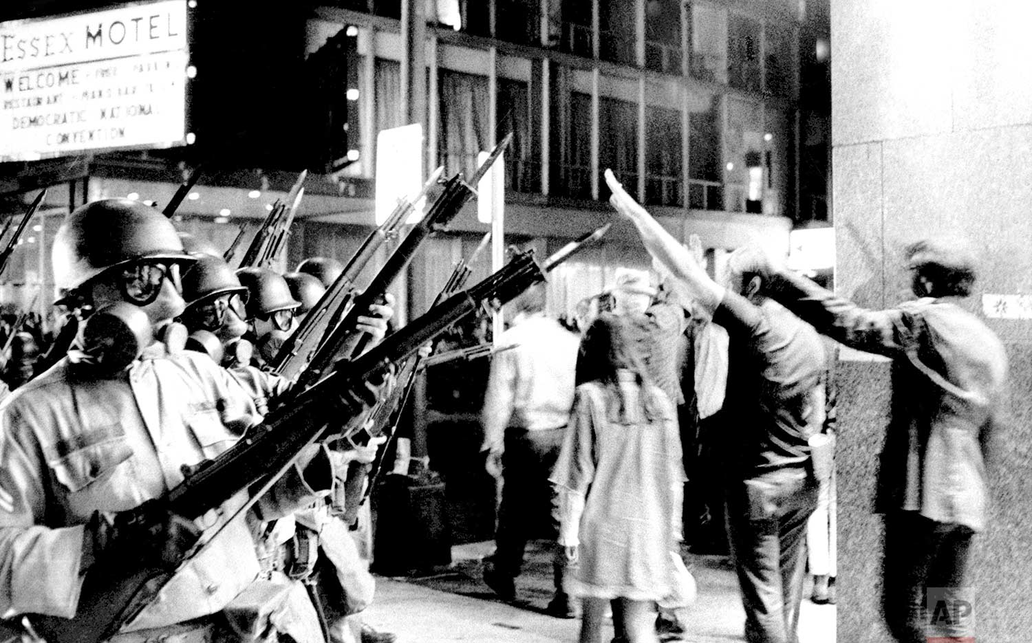 A group of hippies raise their arms in the air and taunt bayonet-armed National Guardsmen near Michigan Avenue in Chicago on August 28, 1968. Police and National Guardsmen battled the demonstrators during the evening. (AP Photo)