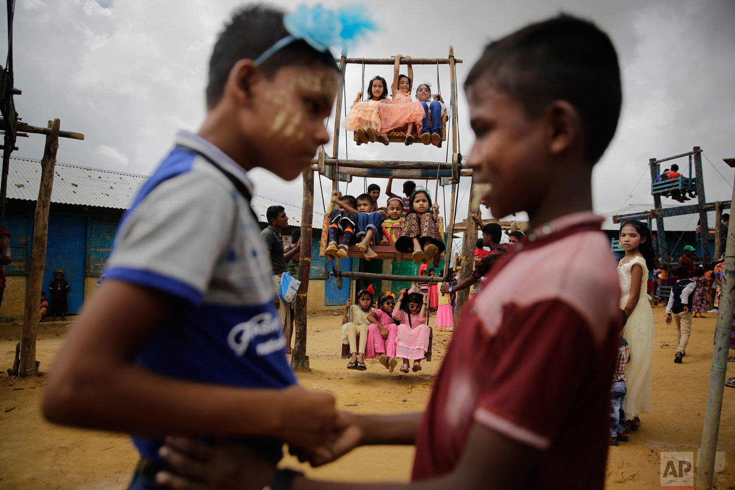 Rohingya refugee boys greet each other as girls ride in a ferris wheel, specially brought in to the camps for Eid al Adha celebrations at the Kutupalong refugee camp, Bangladesh, Wednesday, Aug. 22, 2018. Hundreds of thousands of Rohingya refugees are celebrating Eid al-Adha in sprawling Bangladeshi camps where they have been living amid uncertainty over their future after they fled Myanmar to escape violence and a massive crackdown. (AP Photo/Altaf Qadri)