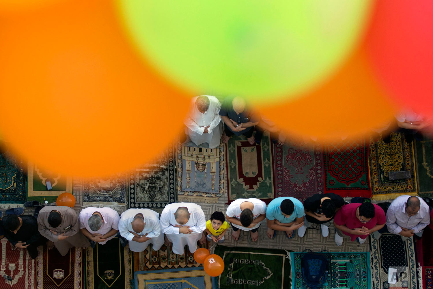 Muslims offer Eid al-Adha prayers outside al-Seddik mosque in Cairo, Egypt, Tuesday, Aug. 21, 2018. During the holiday, which in most places lasts four days, Muslims slaughter sheep or cattle, distribute part of the meat to the poor and eat the rest. (AP Photo/Amr Nabil)