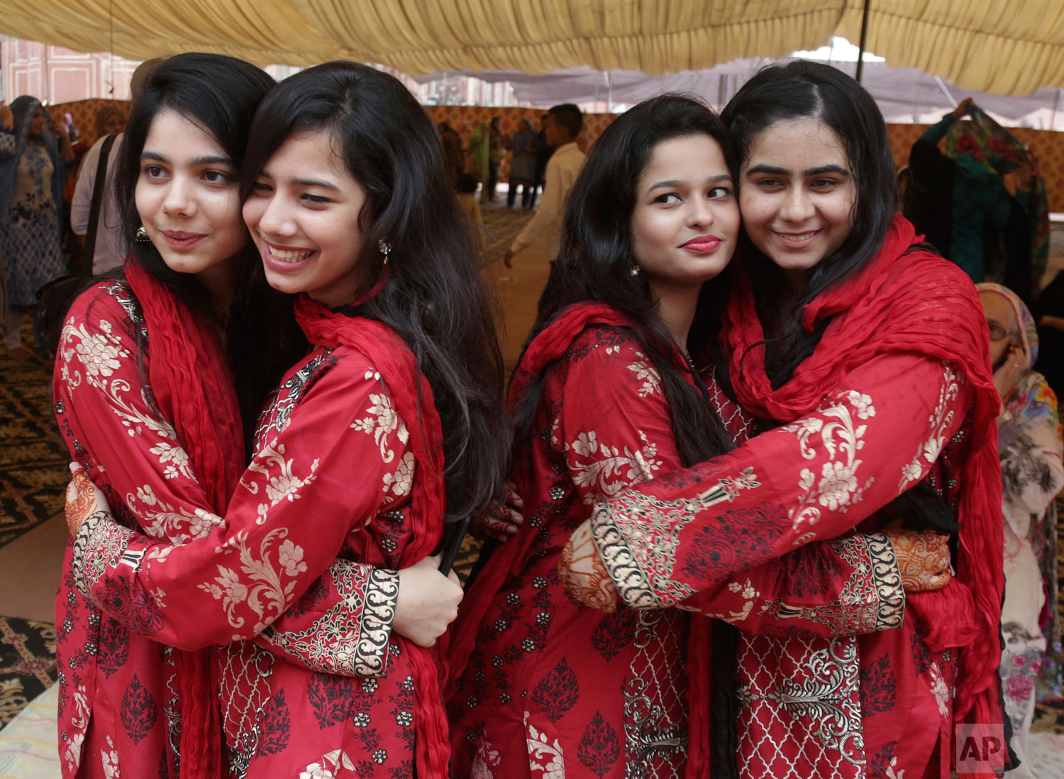 Youths in festive dresses greet each other on the occasion of the Eid al-Adha prayers, in Lahore Pakistan, Wednesday, Aug. 22, 2018. Muslims around the world celebrate Eid al-Adha, or the Feast of the Sacrifice, that marks the willingness of the Prophet Ibrahim (Abraham to Christians and Jews) to sacrifice his son. (AP Photo/K.M. Chaudary)