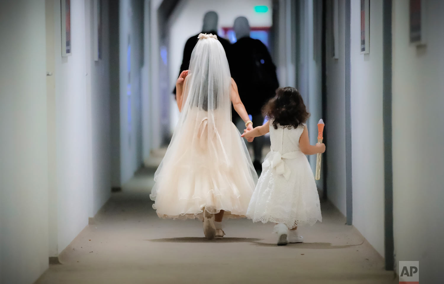 Girls hold hands as they arrive for Eid al-Adha prayers, held in a sports hall in Bucharest, Romania, Tuesday, Aug. 21, 2018. Muslims worldwide are celebrating Eid al-Adha, or the Feast of the Sacrifice, which commemorates the biblical story of Abraham and his readiness to sacrifice his son as an act of obedience to God, by sacrificial killing of sheep, goats, cows or camels. (AP Photo/Vadim Ghirda)