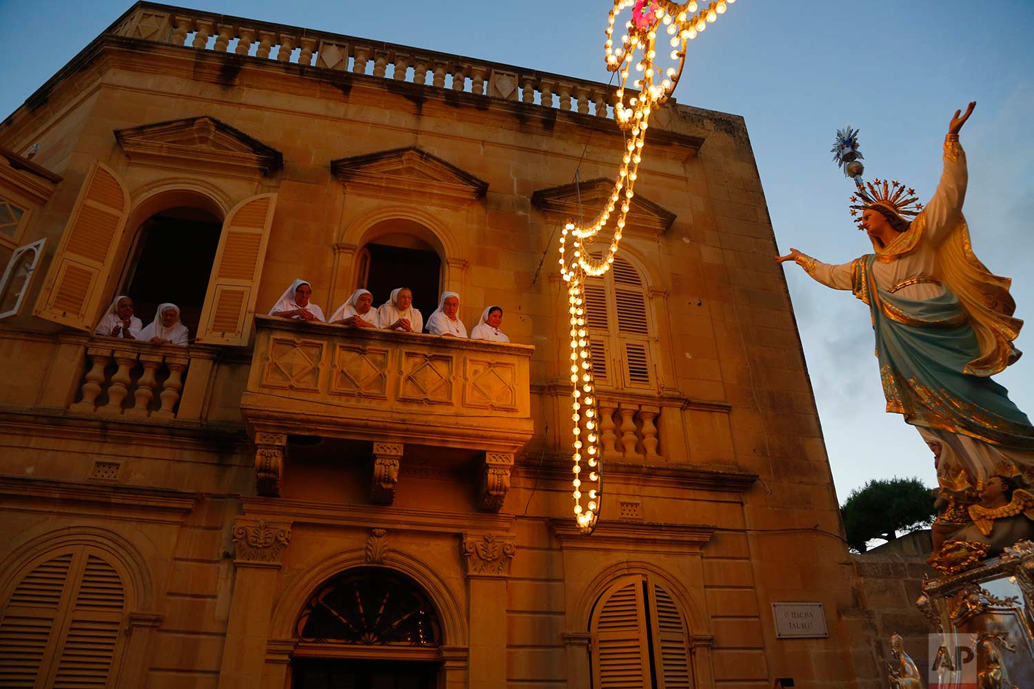 In this photo taken on Wednesday, Aug. 15, 2018, nuns watch the statue of the Virgin Mary being carried through the streets of Rabat on the island of Gozo in the Maltese archipelago, during the feast day of the Assumption of Mary. (AP Photo/Niranjan Shrestha)