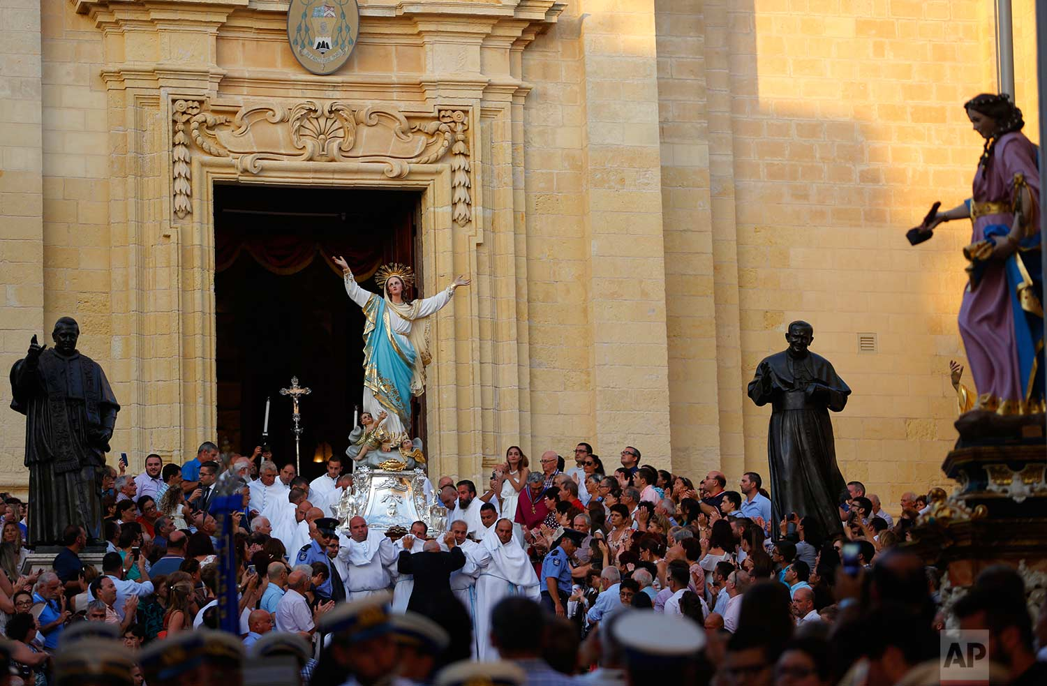 In this photo taken on Wednesday, Aug. 15, 2018, the Statue of the Virgin Mary is taken out from Gozo Cathedral in the old Citadel in Rabat on the island of Gozo in the Maltese archipelago during the feast day of the Assumption of Mary. (AP Photo/Niranjan Shrestha)