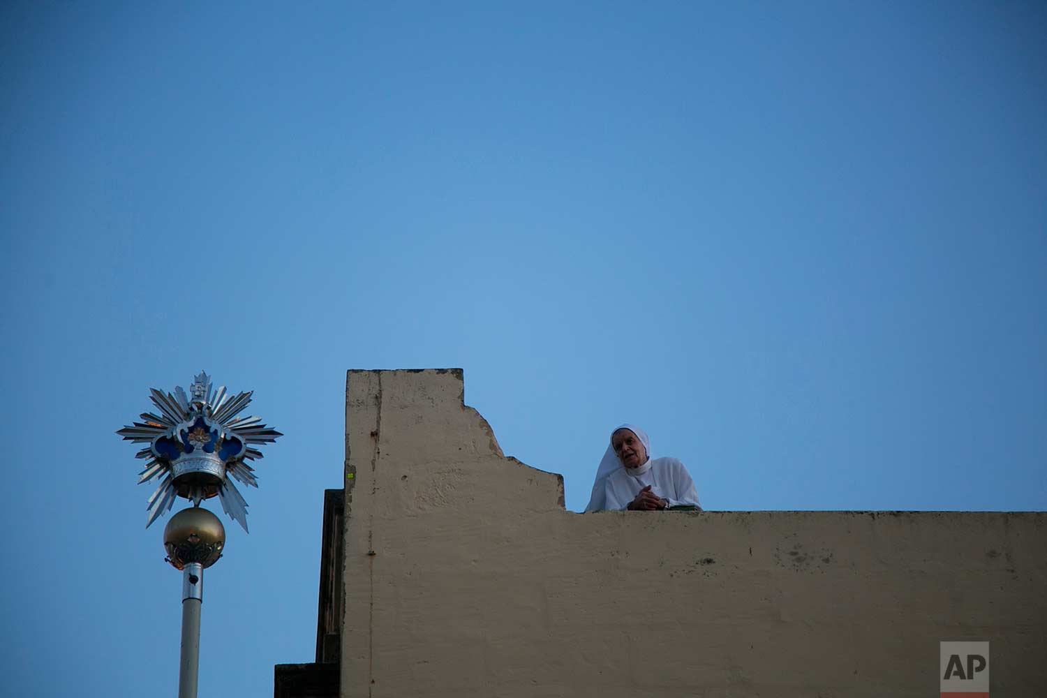 In this photo taken on Wednesday, Aug. 15, 2018, a nun watches the statue of the Virgin Mary being carried through the streets of Rabat on the island of Gozo in the Maltese archipelago, during the feast day of the Assumption of Mary. (AP Photo/Niranjan Shrestha)