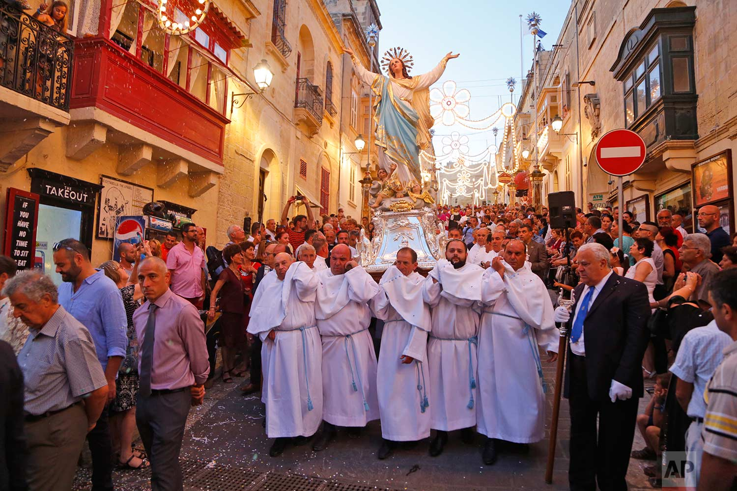 In this photo taken on Wednesday, Aug. 15, 2018, devotees carry a statue of the Virgin Mary through the streets of Rabat on the island of Gozo in the Maltese archipelago, during the feast day of the Assumption of Mary. (AP Photo/Niranjan Shrestha)