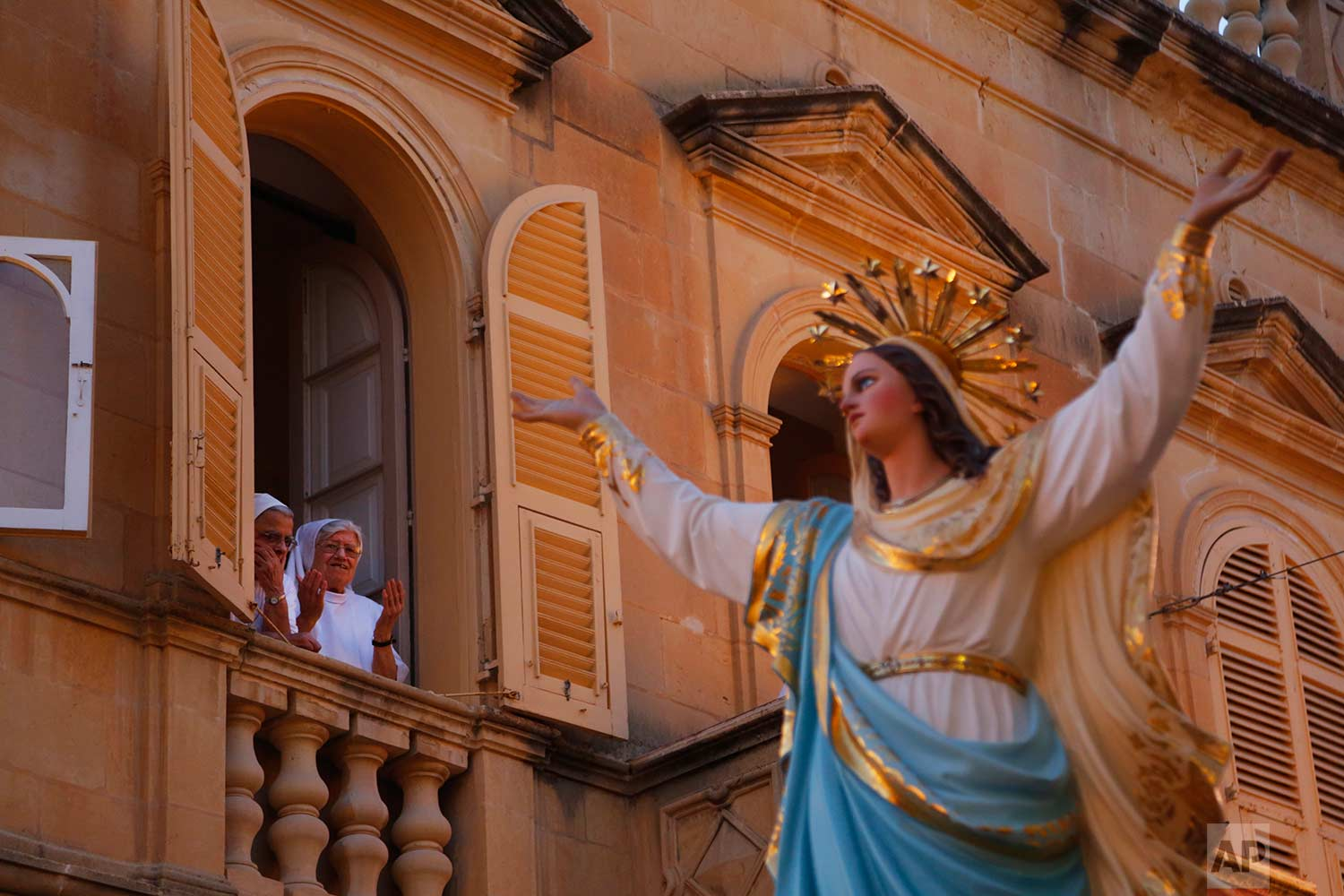 In this photo taken on Wednesday, Aug. 15, 2018, nuns offer a prayer as the statue of the Virgin Mary being carried through the streets of Rabat on the island of Gozo in the Maltese archipelago, during the feast day of the Assumption of Mary. (AP Photo/Niranjan Shrestha)