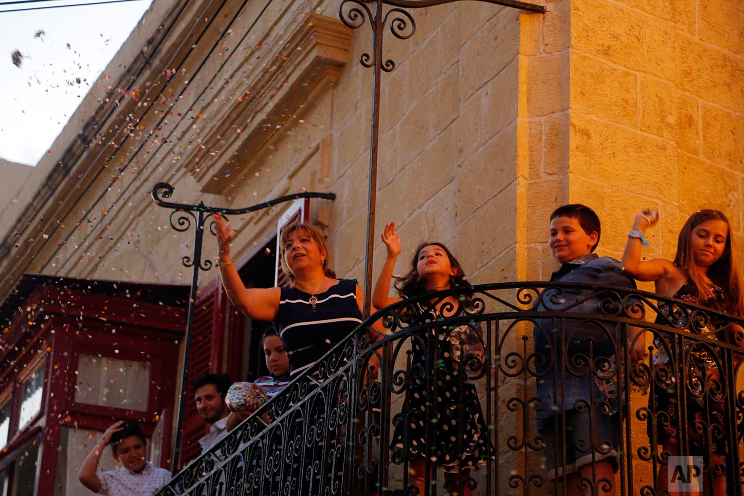 In this photo taken on Wednesday, Aug. 15, 2018, residents throw confetti on the statue of the Virgin Mary as it is carried through the streets of Rabat on the island of Gozo in the Maltese archipelago, during the feast day of the Assumption of Mary. (AP Photo/Niranjan Shrestha)