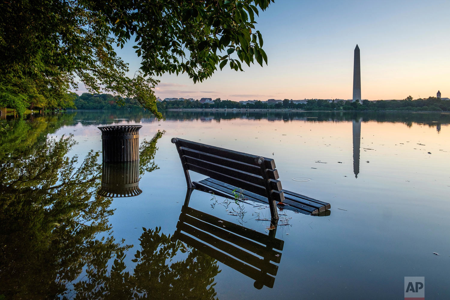 A bench is surrounded by water after recent heavy rains caused the Tidal Basin in Washington to overflow its banks Wednesday, Aug. 22, 2018. (AP Photo/J. David Ake)