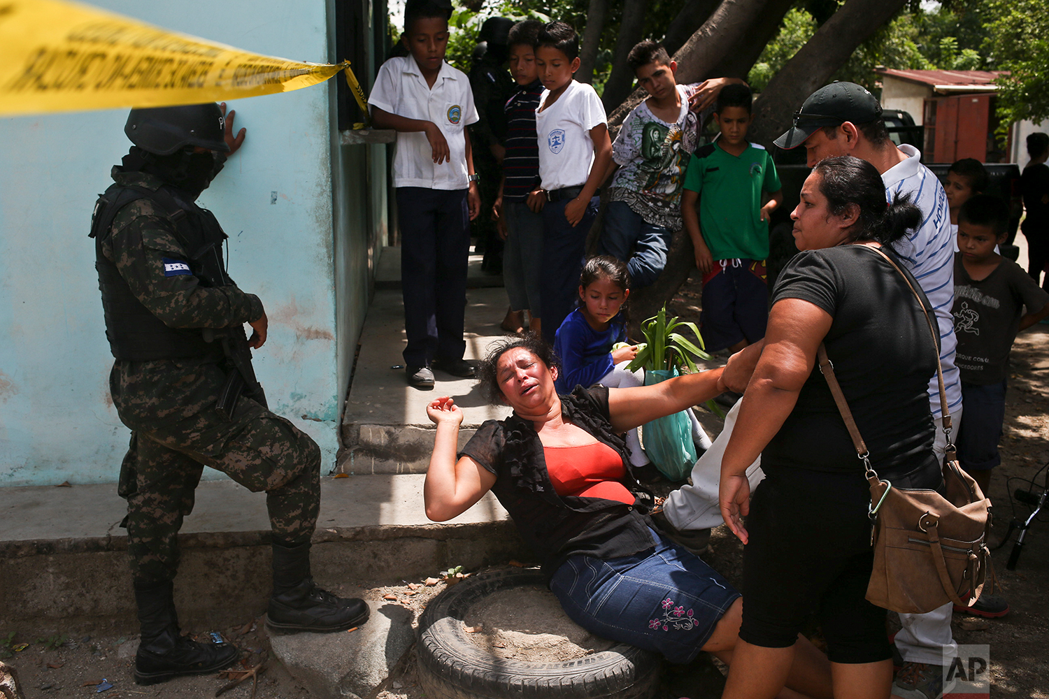 In this July 9, 2018 photo, a woman breaks down crying on the perimeter of a crime scene where her only son Javier Antonio Santos, 18, was killed during a shootout with military police, where an officer also died, in the Chamelecon neighborhood of San Pedro Sula, Honduras. The two youths who died in the shootout are alleged by police to be Mara gang members, while the mother cried that he was not. (AP Photo/Esteban Felix)