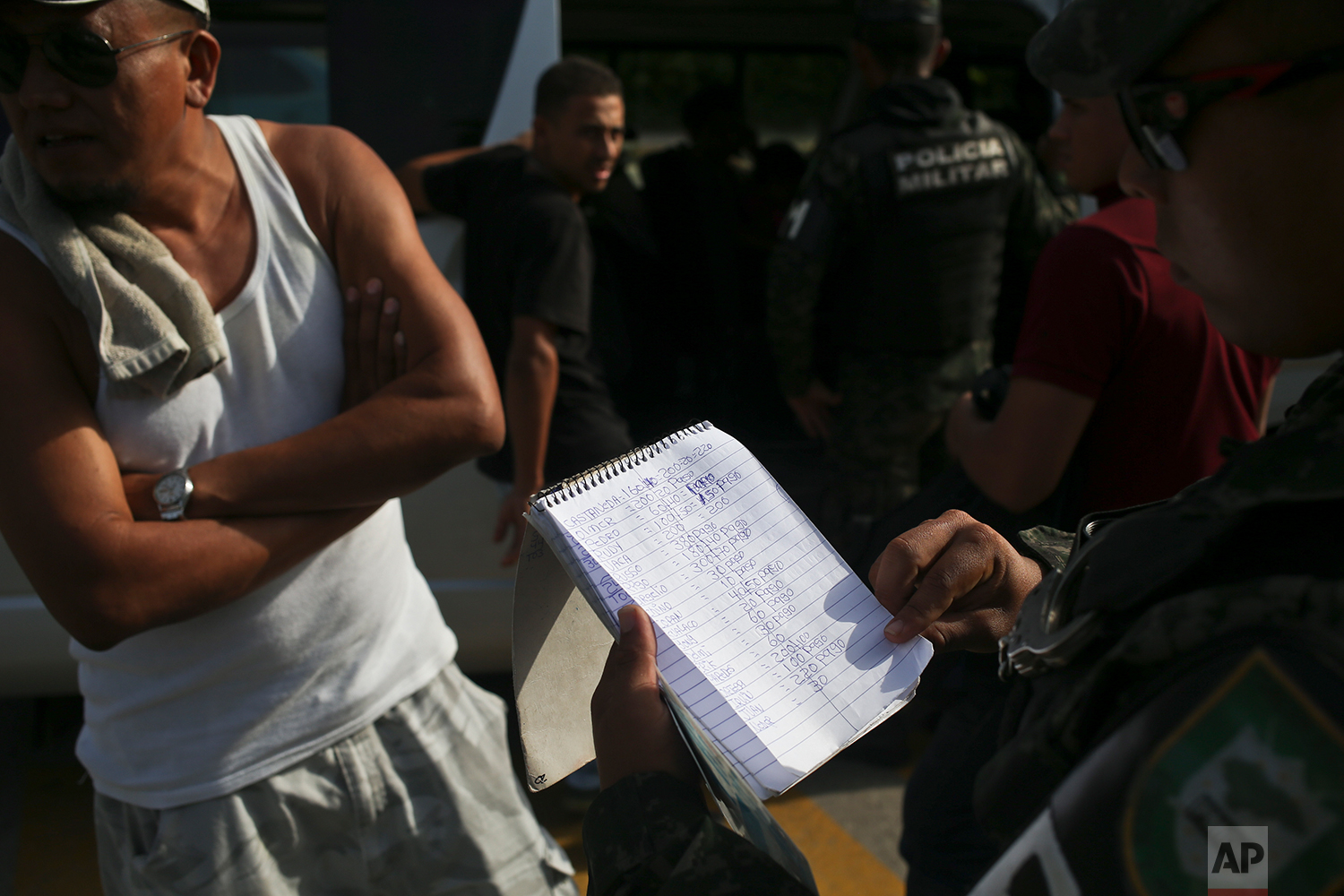In this July 4, 2018 photo, a military police officer looks at a notebook found hidden inside a public bus, as he searches several men who were the bus in San Pedro Sula, Honduras. The notebook, which no one claimed to be the owner of, appears to list names and extortion payments, due and paid, by shop owners, drivers, etc. No one was detained during the search of bus passengers, but the notebook was confiscated by police. (AP Photo/Esteban Felix)