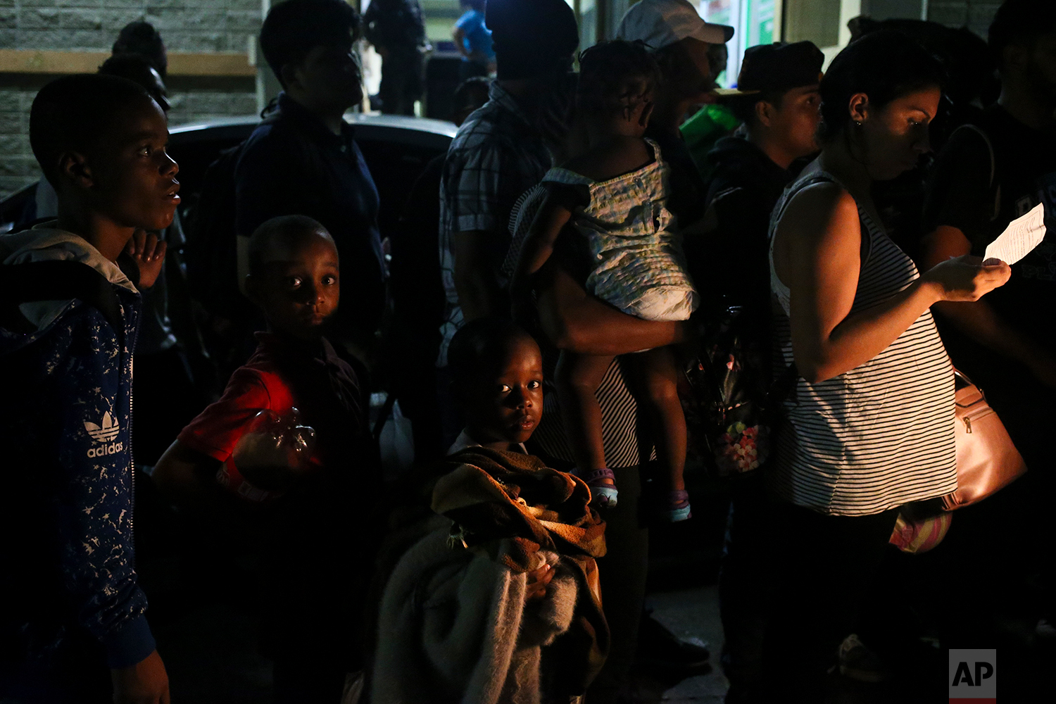In this July 4, 2018 photo, child migrants traveling with their parents line up to get on a bus destined for Guatemala City as they make their way to the U.S., in San Pedro Sula, Honduras. In 2018, the Honduran Migration Consular Observatory (CONMIGHO) counted 5,488 minors deported back to Honduras from the U.S., Mexico, Europe and Central America. (AP Photo/Esteban Felix)