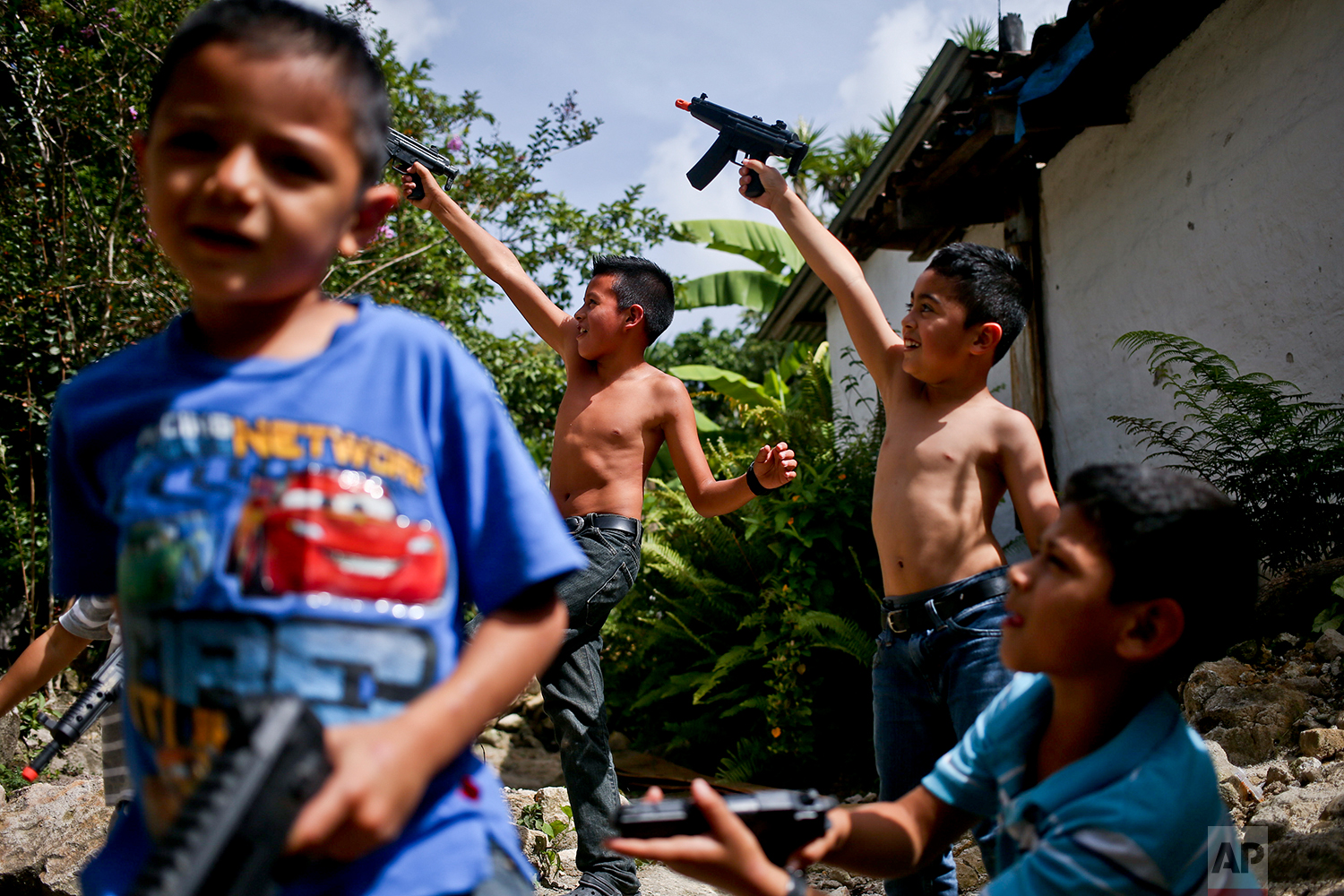 """In this July 22, 2018 photo, brothers and cousins pretend to shoot little girls watching them from a window, as they play cops and gangsters with toy guns that were a gift from an uncle, in Taulabe, Honduras. When asked if they were cops or gangsters, they paused to think about it and answered """"cops."""" (AP Photo/Esteban Felix)"""