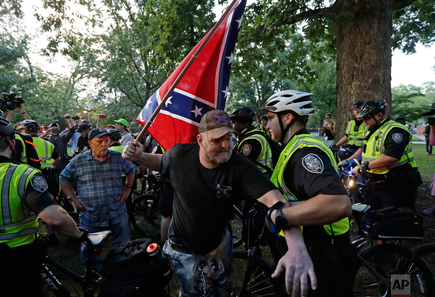 """A police officer grabs a man holding a Confederate flag during a rally for the recently vandalized Confederate monument known as """"Silent Sam"""" at the University of North Carolina in Chapel Hill, N.C., Thursday, Aug. 30, 2018. (AP Photo/Gerry Broome)"""