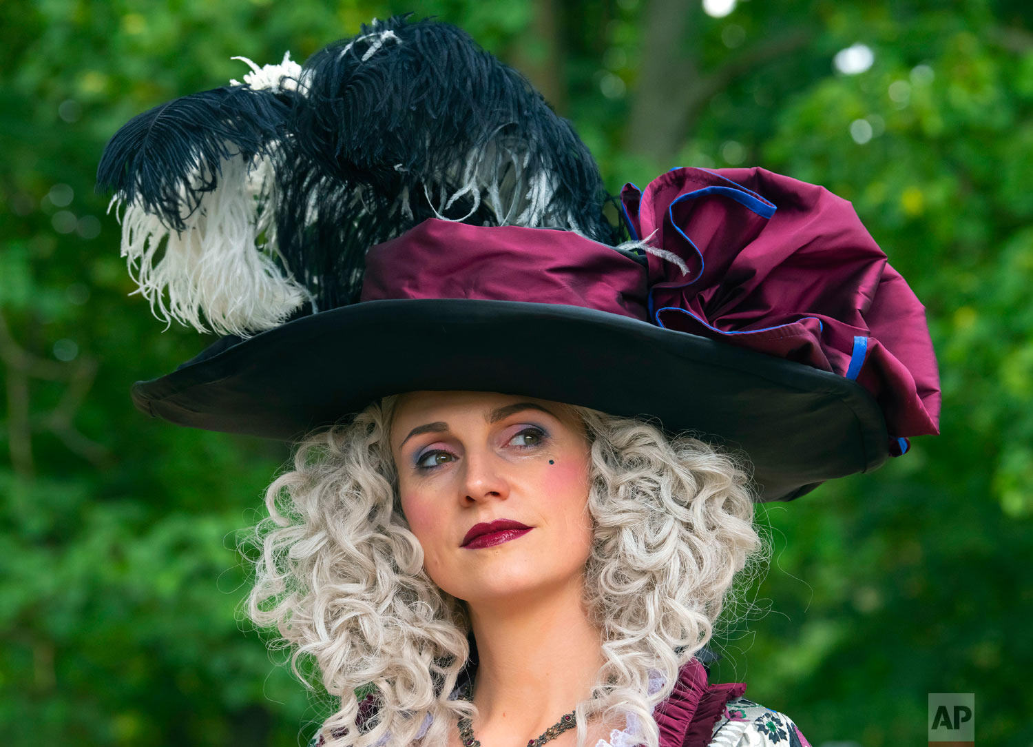 A woman dressed in traditional clothing takes part in the picnic near the Friedenstein Castle, during the Baroque Festival in Gotha, Germany, Saturday, Aug. 25, 2018. For the past fifteen years, the city transforms into an 18th Century city for the annual festival. (AP Photo/Jens Meyer)