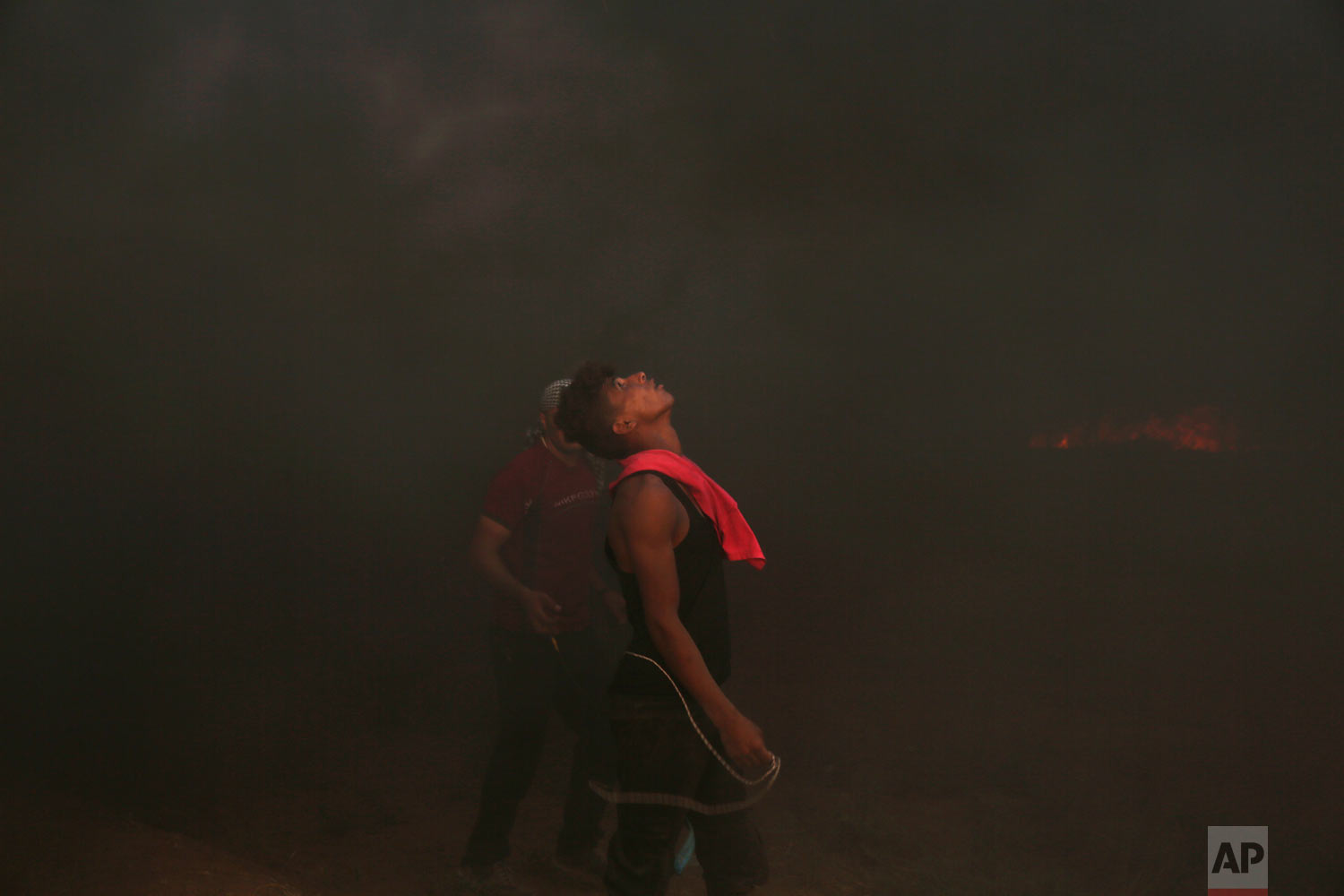 Protesters burn tires near the fence of the Gaza Strip border with Israel, during a protest east of Gaza City, Friday, Aug. 31, 2018. Gaza's Health Ministry says Israeli gunfire wounded about 80 Palestinians at the weekly protest along the border with Israel. Senior Hamas leader Khalil al-Hayya has said the weekly protests would only stop when Israel lifts its siege on Gaza. (AP Photo/Adel Hana)
