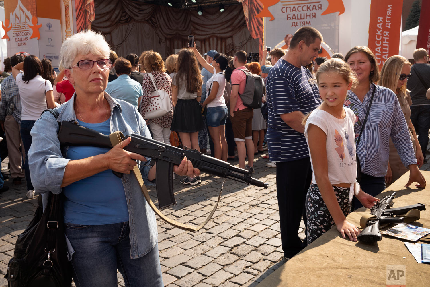 A woman holds a Kalashnikov assault rifle during the Spasskaya Tower international military music festival in Red Square in Moscow, Russia, Friday, Aug. 31, 2018. (AP Photo/Alexander Zemlianichenko)