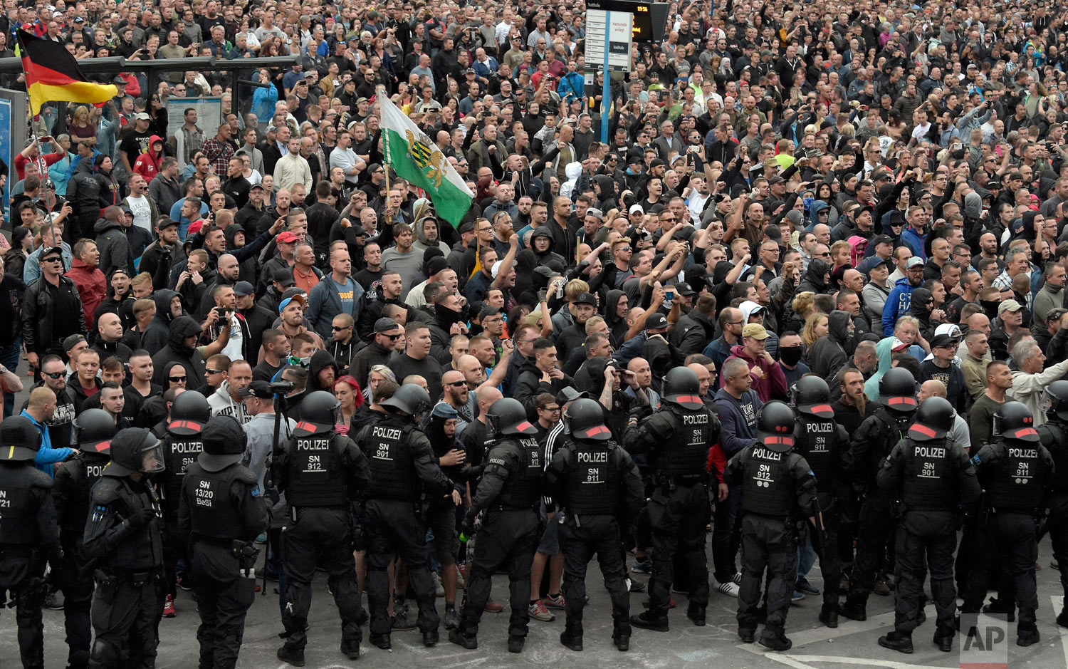 """Demonstrators shout during a far-right protest in Chemnitz, Germany, Monday, Aug. 27, 2018 after a man died and two others were injured in an altercation between several people of """"various nationalities"""" in the eastern German city of Chemnitz on Sunday. (AP Photo/Jens Meyer)"""
