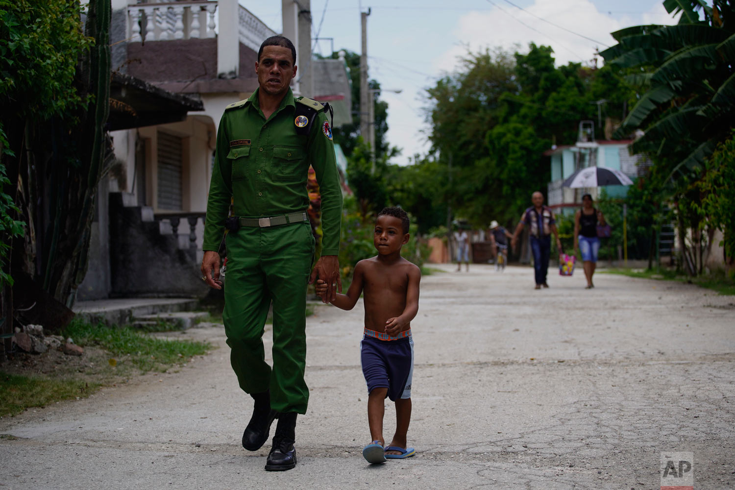 In this July 25, 2018 photo published in August, a Cuban special brigade first lieutenant police officer walks with his son to a neighborhood party where they will cook a large stew, in Guantanamo, Cuba, near the U.S. naval base. It is tradition in Cuba for neighbors to pool their efforts to cook a large stew, using pork. (AP Photo/Ramon Espinosa)