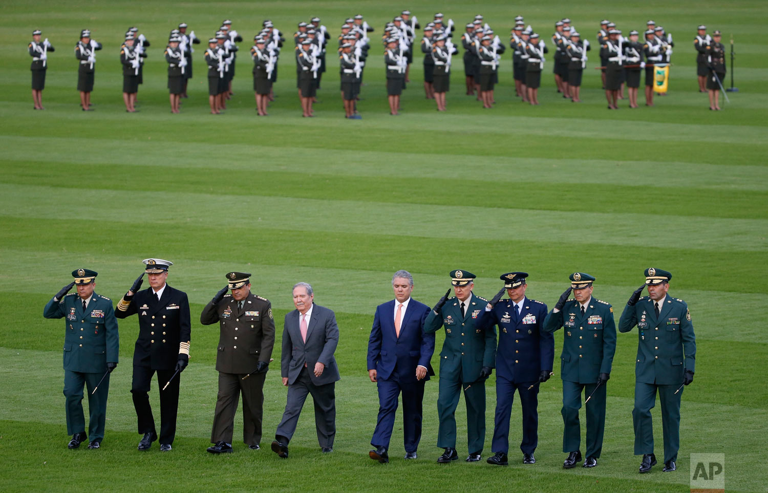 Colombia's President Ivan Duque, fifth from left, walks with his new Defense Minister Guillermo Botero, fourth from left, as they review troops with military officials during a ceremony in Bogota, Colombia, Aug. 14, 2018. At the ceremony, Botero formally took command of the armed forces. (AP Photo/Fernando Vergara)