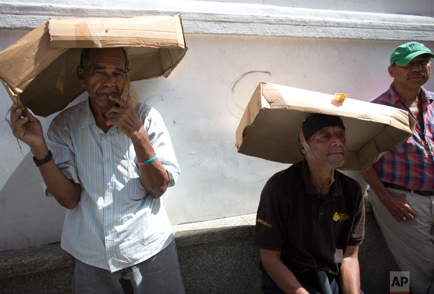 Men utilize cardboard boxes to shade themselves from the sun's rays sun as they wait in line to take part in a vehicle census announced by Venezuela President Nicolas Maduro, as a first step to regulate the sale of gasoline, at Bolivar Square in Caracas, Venezuela, Aug. 3, 2018. The census started today. (AP Photo/Ariana Cubillos)