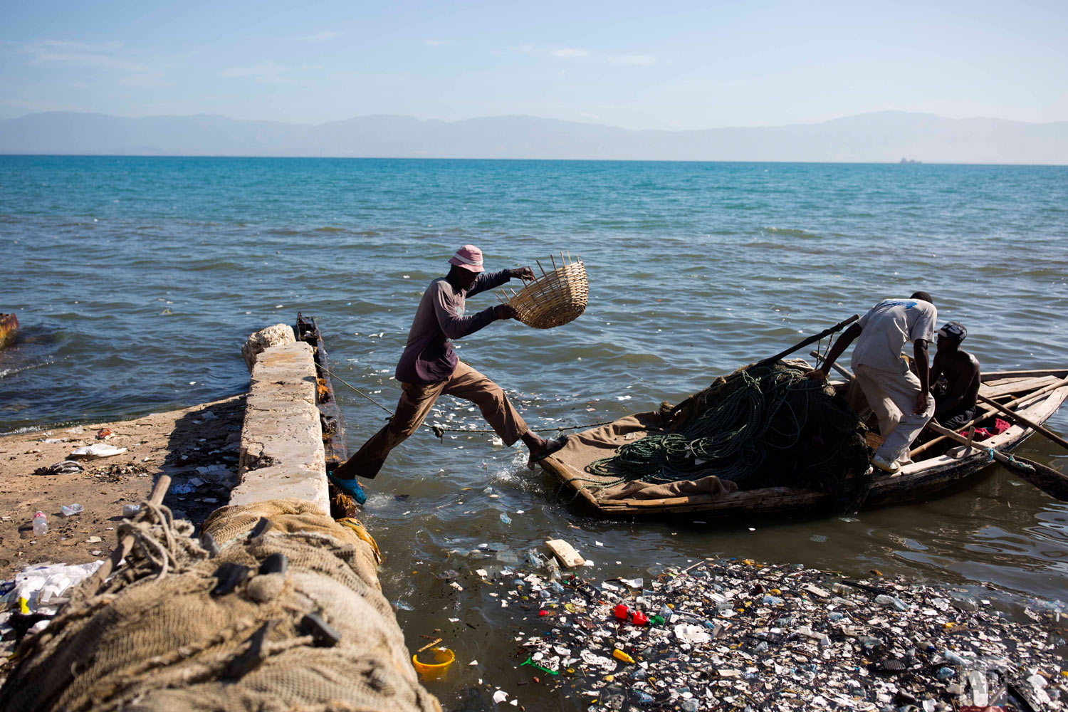 A fisherman jumps on to his wooden boat, joining his mates as they head out to the sea from Port-au-Prince, Haiti, Aug. 13, 2018. (AP Photo/Dieu Nalio Chery)