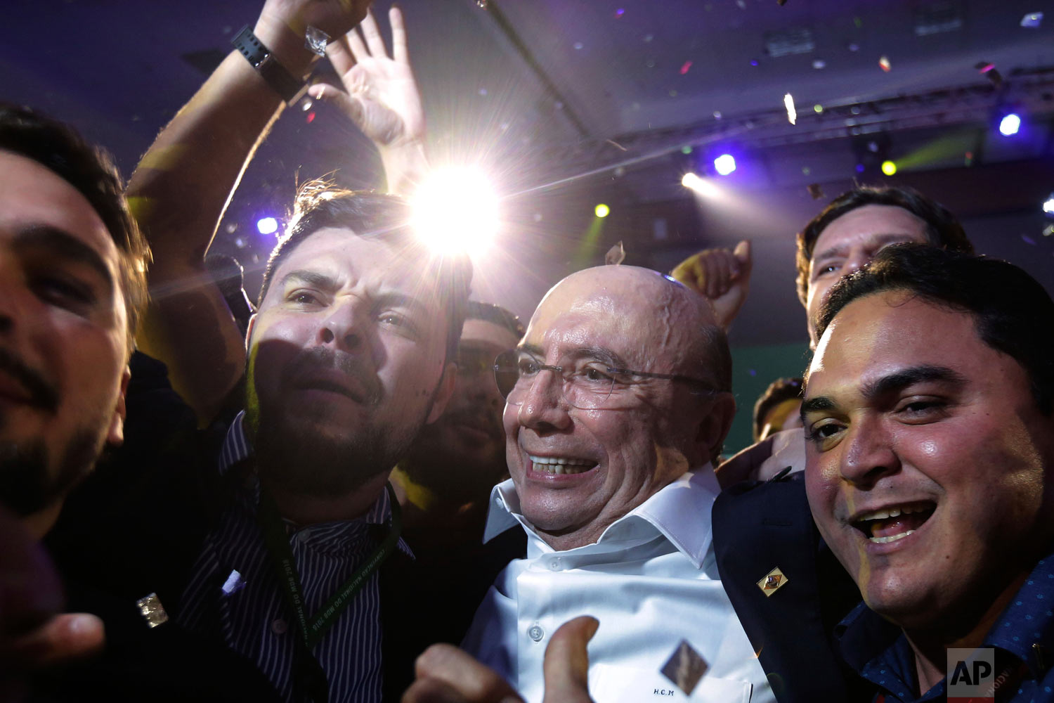 Brazil's former finance minister Henrique Meirelles, center, celebrates with supporters at the end of The Brazilian Democratic Movement party convention, in Brasilia, Brazil, Aug. 2, 2018. The Brazilian Democratic Movement announced Meirelles as its candidate for the upcoming October election. (AP Photo/Eraldo Peres)