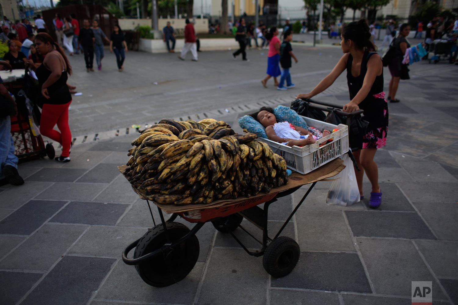 A street vendor pushes a wheelbarrow on which her baby daughter sleeps next to plantains for sale, at a central plaza in San Salvador, El Salvador, Aug. 19, 2018. Earlier this year, the capital opened its newly-renovated downtown heart, with a pedestrian zone linking several updated squares in the capital's historic center. Where public transit buses and market stalls once clogged the streets, local residents enticed by both new amenities and greater security now stroll, watch street concerts, or play in the illuminated water fountain. No longer authorized to have fixed stands, vendors can operate as long as they keep moving. (AP Photo/Rebecca Blackwell)