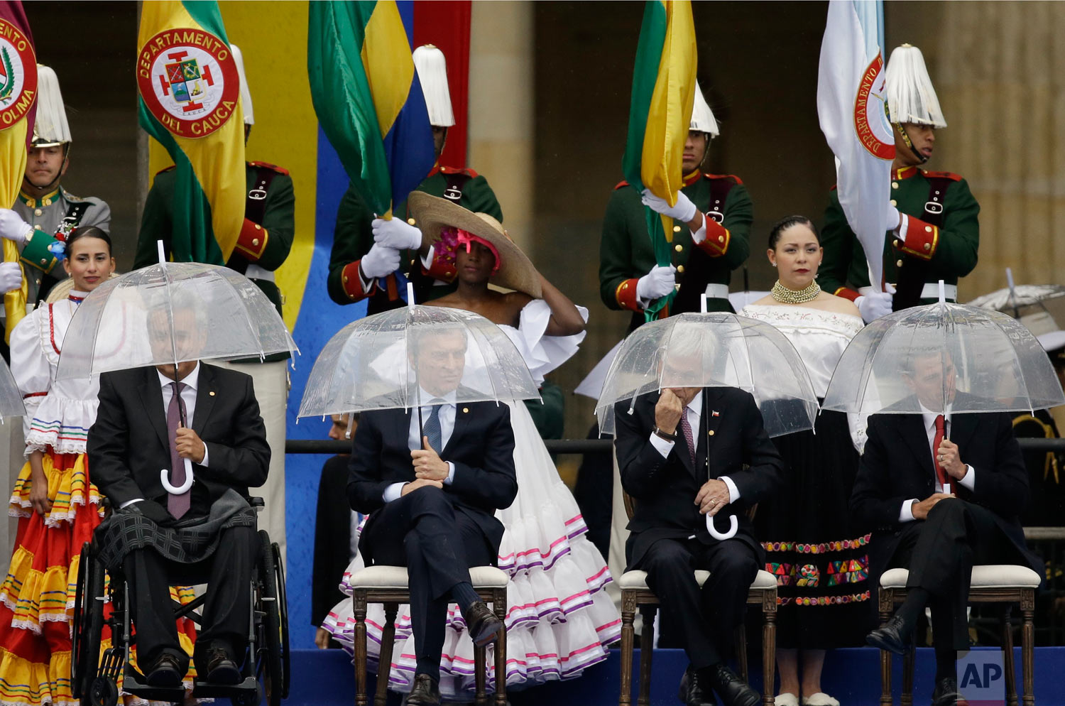 Leaders, from left, Ecuador's President Lenin Moreno, Argentina's President Mauricio Macri, Chile's President Sebastian Pinera and Mexico's President Enrique Pena Nieto use umbrellas as it rains during the inauguration ceremony for Colombia's new President Ivan Duque in Bogota, Colombia, Aug. 7, 2018. The young protégé of a powerful former president was sworn in as Colombia's new leader Tuesday, tasked with guiding the implementation of a peace accord with leftist rebels that remains on shaky ground. (AP Photo/Fernando Vergara)