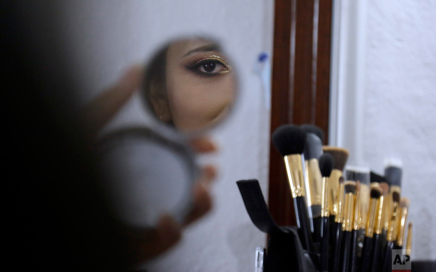 Mariuxi Hinojosa representing the Waranka people, watches herself in a mirror before her presentation in the election of Sara Nusta, or Indigenous Queen pageant, in Quito, Ecuador Aug. 31, 2018. Indigenous women form different ethnicities participated in this annual event to elect the most beautiful indigenous woman of the country. (AP Photo/Dolores Ochoa)