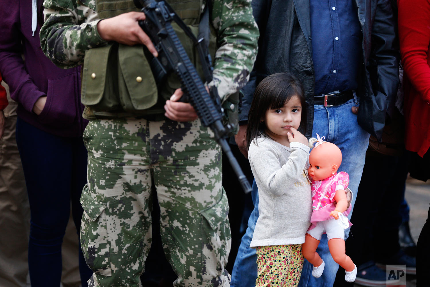 A girl holding her doll watches a military parade marking the 481th anniversary of the founding of Asuncion, Paraguay, Aug. 15, 2018. Paraguay's new President Mario Abdo Benitez was sworn-in before the parade. (AP Photo/Jorge Saenz)
