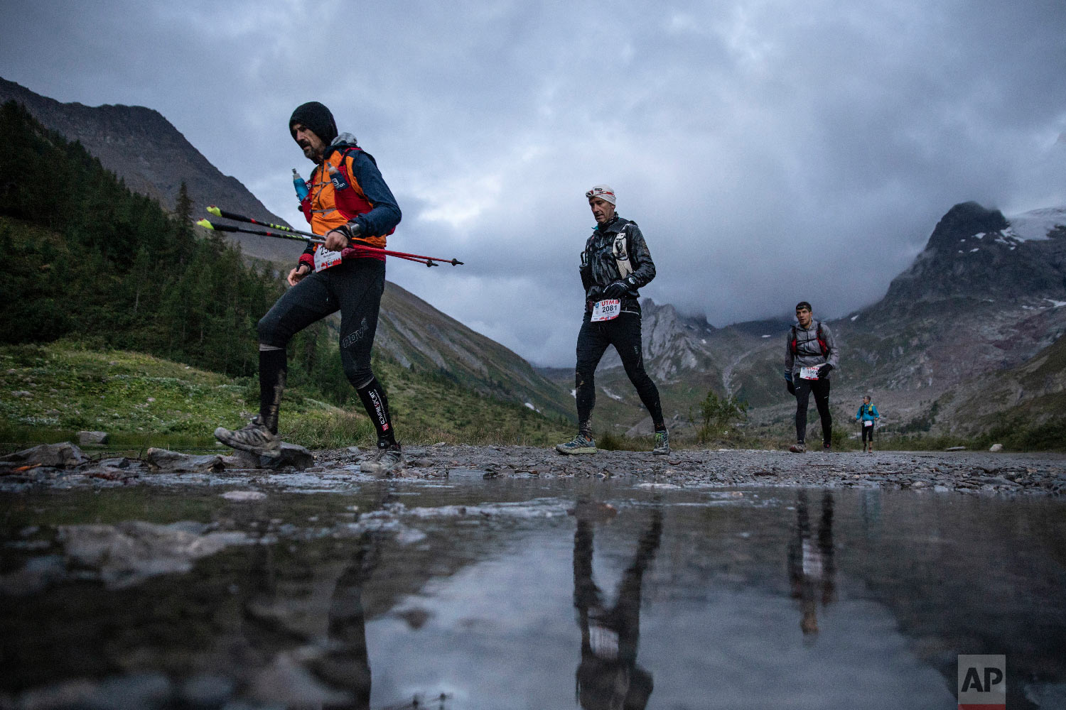 Competitors run next to the Combal lake as they compete in the 170km Ultra-Trail of Mont-Blanc (UTMB) race, in Courmayeur, Italy, Sept 1, 2018. (AP Photo/Laurent Cipriani)