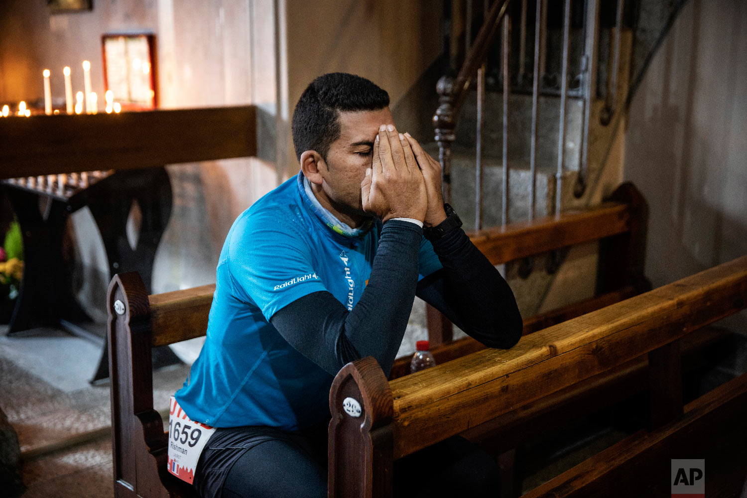 Rishman Lauret of France prays at the Saint Michel church in Chamonix, French Alps, before taking the start of the 170km Ultra-Trail of Mont-Blanc (UTMB) race around the Mont-Blanc, crossing France, Italy and Switzerland, Aug. 31, 2018. (AP Photo/Laurent Cipriani)