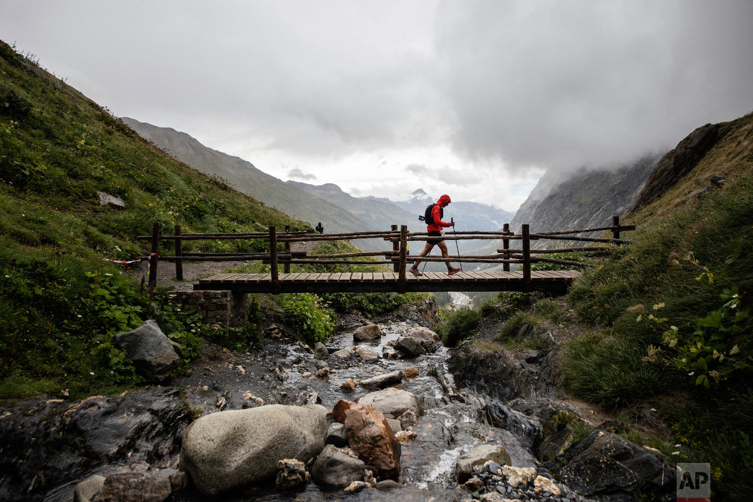 A competitor walks over a bridge on the Grand Col Ferret as he competes in the 170km Ultra-Trail of Mont-Blanc (UTMB) race, near Courmayeur, Italy, Sept 1, 2018. (AP Photo/Laurent Cipriani)