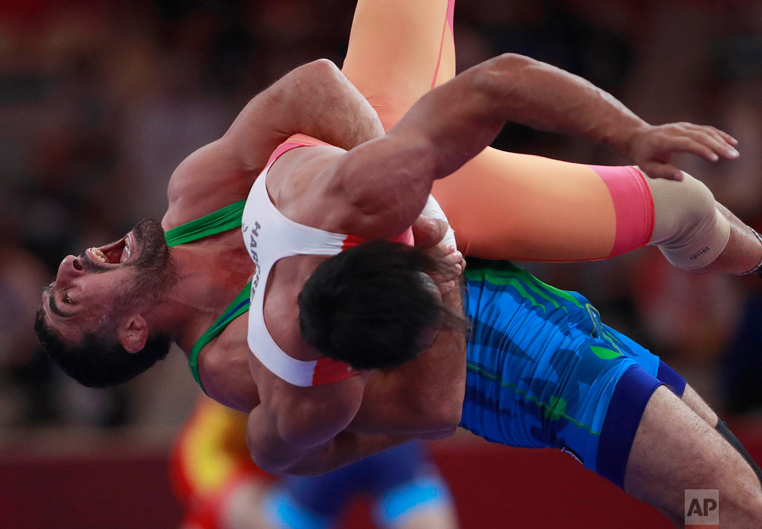 Uzbekistan's Rustam Assakalov, in blue,compete India's Harpreet Singh during their men's Greco-Roman 87-kilogram semi final wrestling match at the 18th Asian Games in Jakarta, Indonesia, Wednesday, Aug. 22, 2018.(AP Photo/Tatan Syuflana)