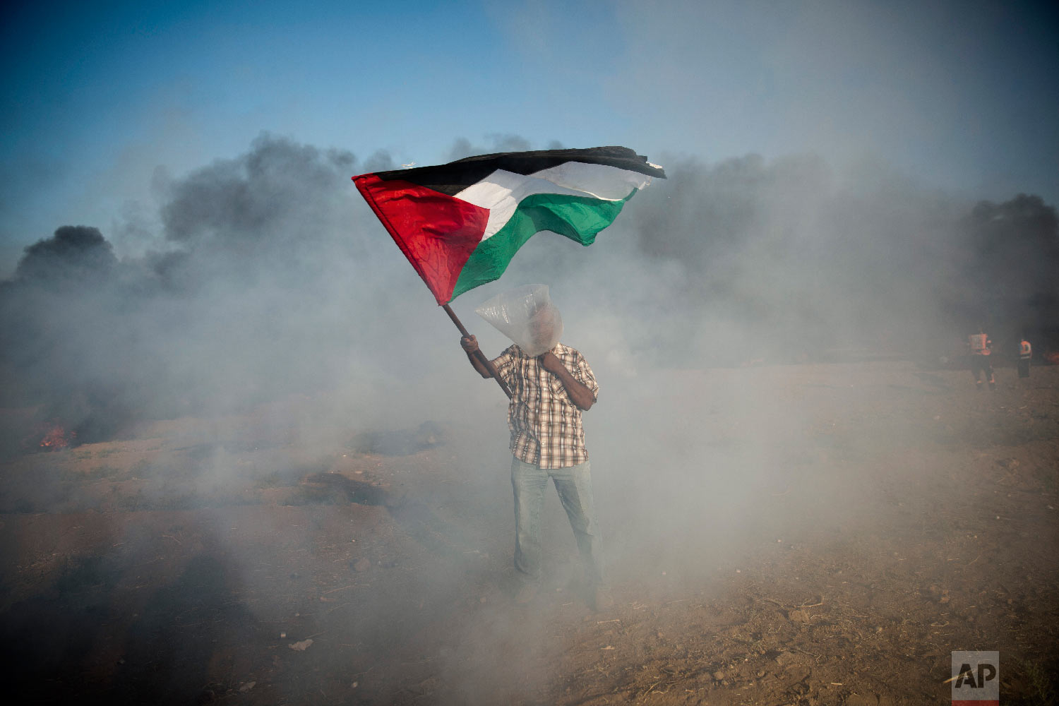 A Palestinian protester wears a plastic bag on his head as a protection from teargas, waves a national flag during a protest at the Gaza Strip's border with Israel, Friday, Aug.10, 2018. (AP Photo/Khalil Hamra)