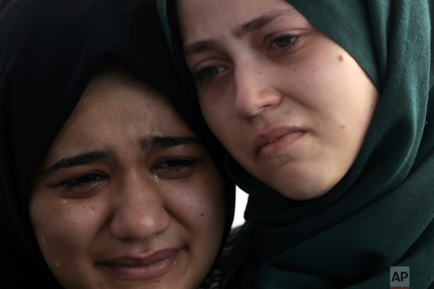 Relatives of Palestinian paramedic Abdullah al-Qutati, who was shot and killed during the Friday's protest at the Gaza Strip's border with Israel, mourn in the family home during his funeral in town of Rafah, southern Gaza Strip, Saturday, Aug.11, 2018. (AP Photo/Khalil Hamra)