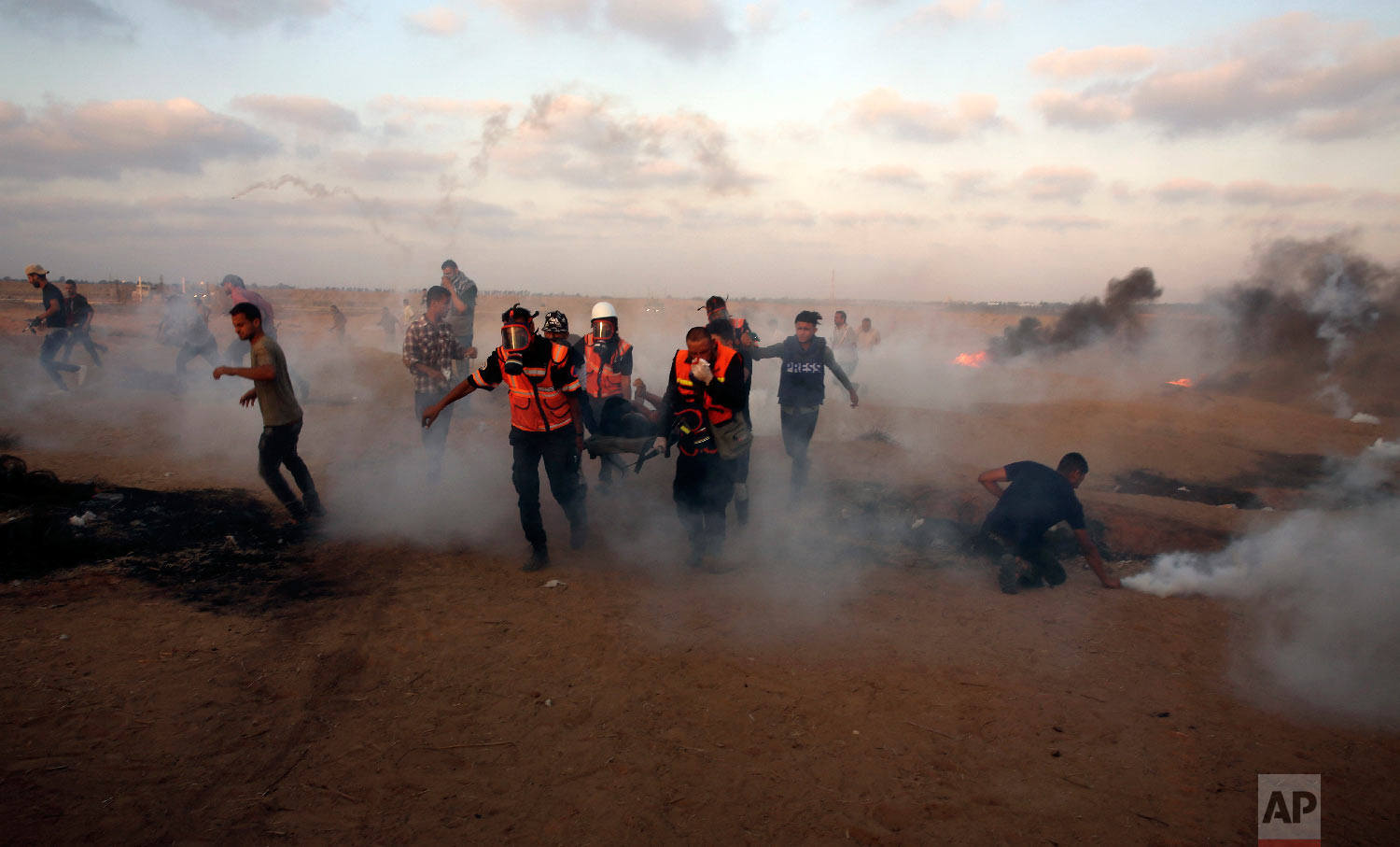 Medics evacuate a wounded youth while others run to cover from teargas fired by Israeli troops near the Gaza Strip border with Israel, during a protest east of Khan Younis, southern Gaza Strip, Friday, Aug. 24, 2018. (AP Photo/Adel Hana)