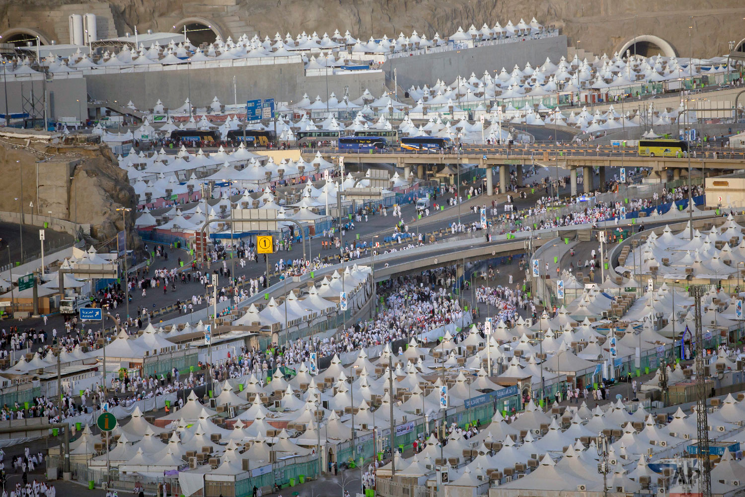 Muslim pilgrims walk back to their tents during the annual Hajj pilgrimage on the first day of Eid al-Adha in Mina, outside the holy city of Mecca, Saudi Arabia, Tuesday, Aug. 21, 2018. The five-day pilgrimage represents one of the five pillars of Islam and is required of all able-bodied Muslims once in their life. (AP Photo/Dar Yasin)