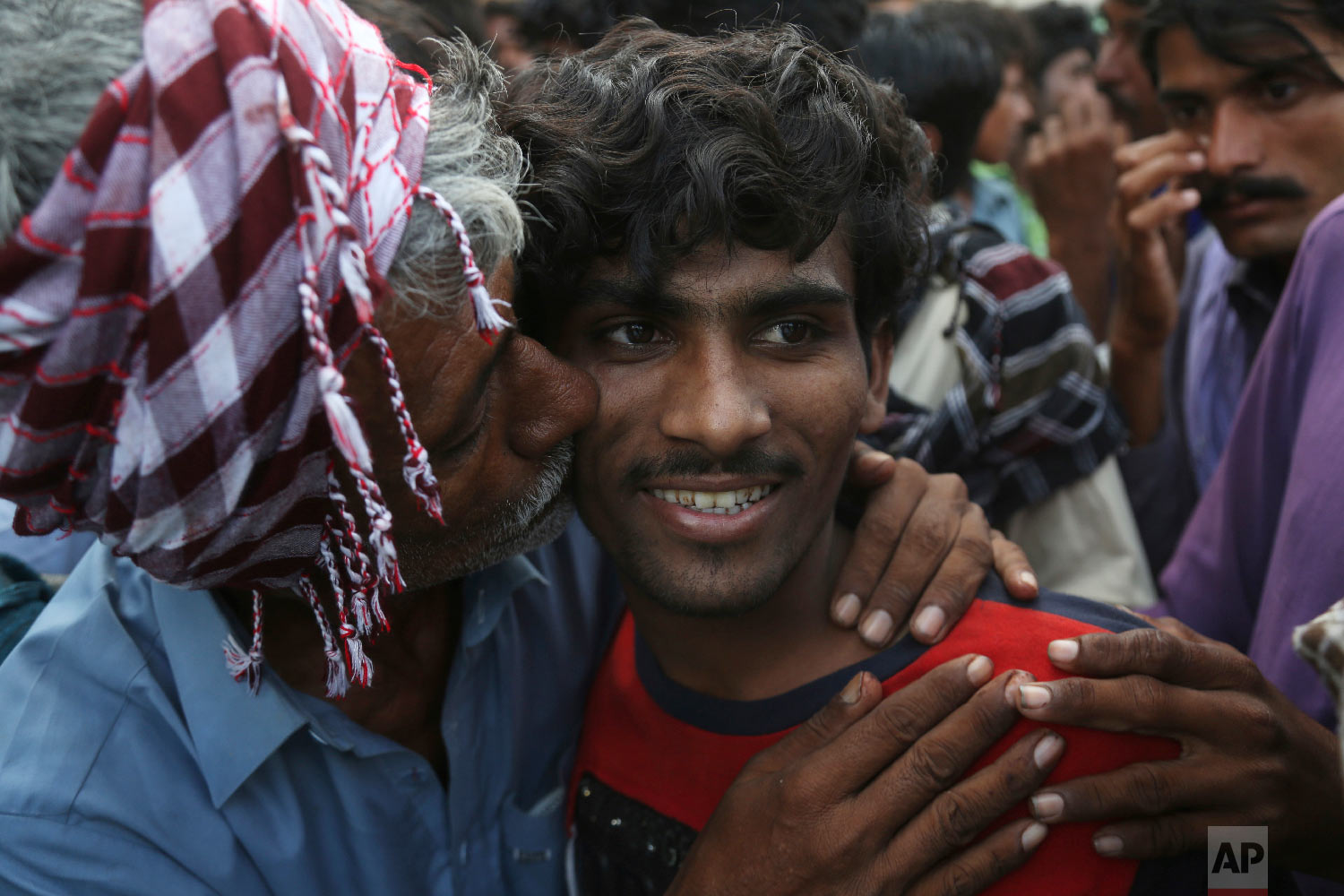 Pakistani family members receive a fisherman, center, who is released by Indian authorities, at Karachi railway station in Karachi, Pakistan, Friday, Aug. 10, 2018. The Indian government has released 14 Pakistani fishermen held for violating its territorial waters as a goodwill gesture. (AP Photo/Shakil Adil)