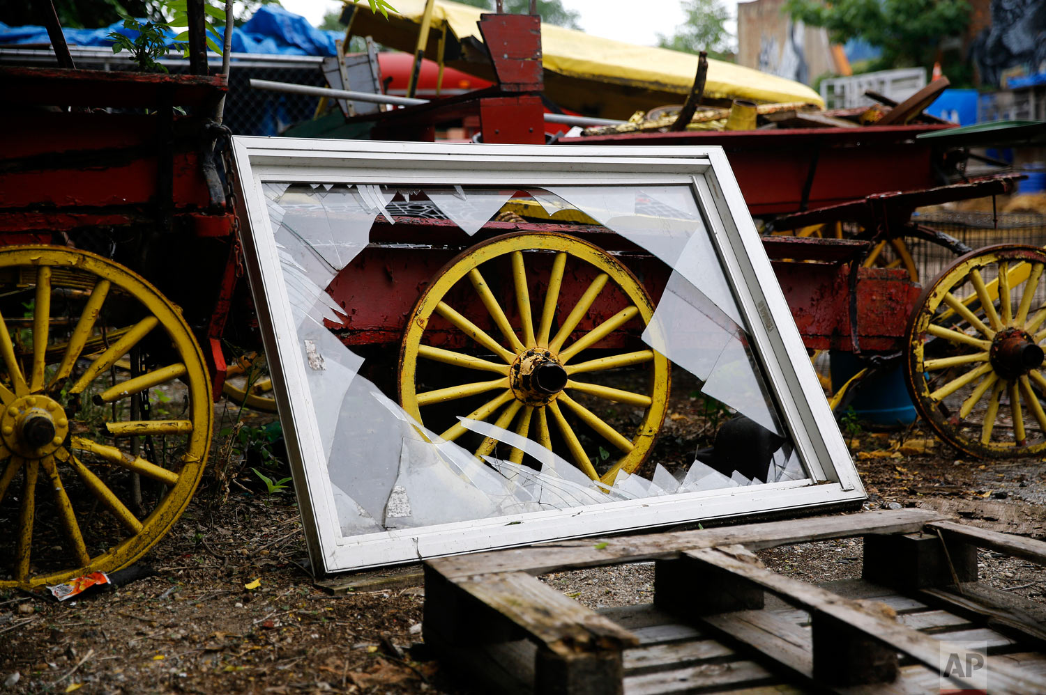 A broken window rests against a disused horse-drawn cart at an arabber stable in Baltimore in this June 18, 2018, photo. (AP Photo/Patrick Semansky)