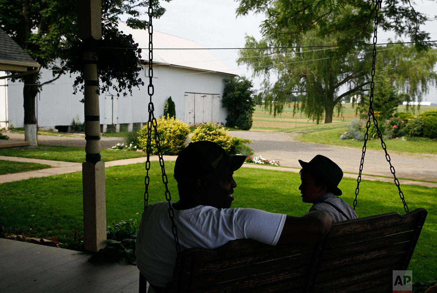James Chase, left, the leader of a Baltimore arabber stable, visits with a member of an Old Order Mennonite family on June 18, 2018, at the family's farm in New Holland, Pennsylvania. (AP Photo/Patrick Semansky)