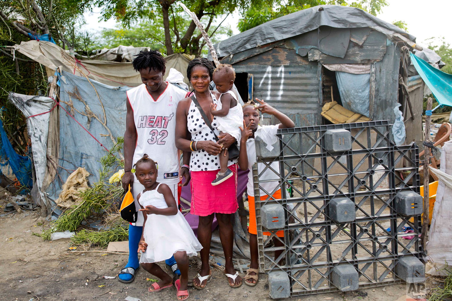 Changlair Aristide stands with his wife Violene Mareus and daughters outside their home before leaving to play soccer. 9-year-old Changline stands at right. 3-year-old Belinda is held by her mother. 5-year-old Viergeline stands below. Aug. 29, 2018. (AP Photo/Dieu Nalio Chery)