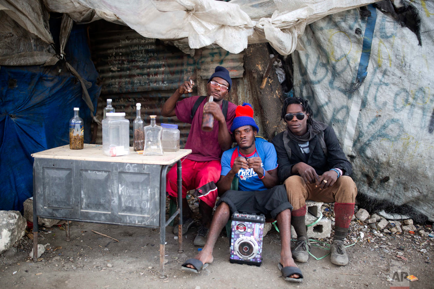 """Trash scavengers rest at a spot coined """"Anba pye bwa"""" in Creole, or """"Under the tree"""" after a long day at the dump. Aug. 30, 2018. (AP Photo/Dieu Nalio Chery)"""
