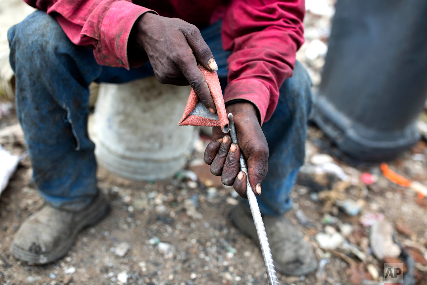 Changlair Aristide sharpens a metal rod he uses to pick through the rubble. Aug. 23, 2018. (AP Photo/Dieu Nalio Chery)