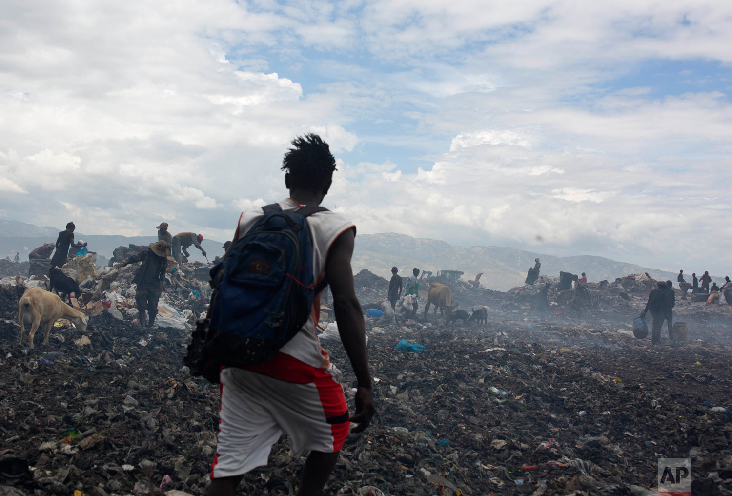 Changlair Aristide crosses the landfill after a day of scavenging trash, as he makes his way to meet with friends. Aug. 27, 2018. (AP Photo/Dieu Nalio Chery)