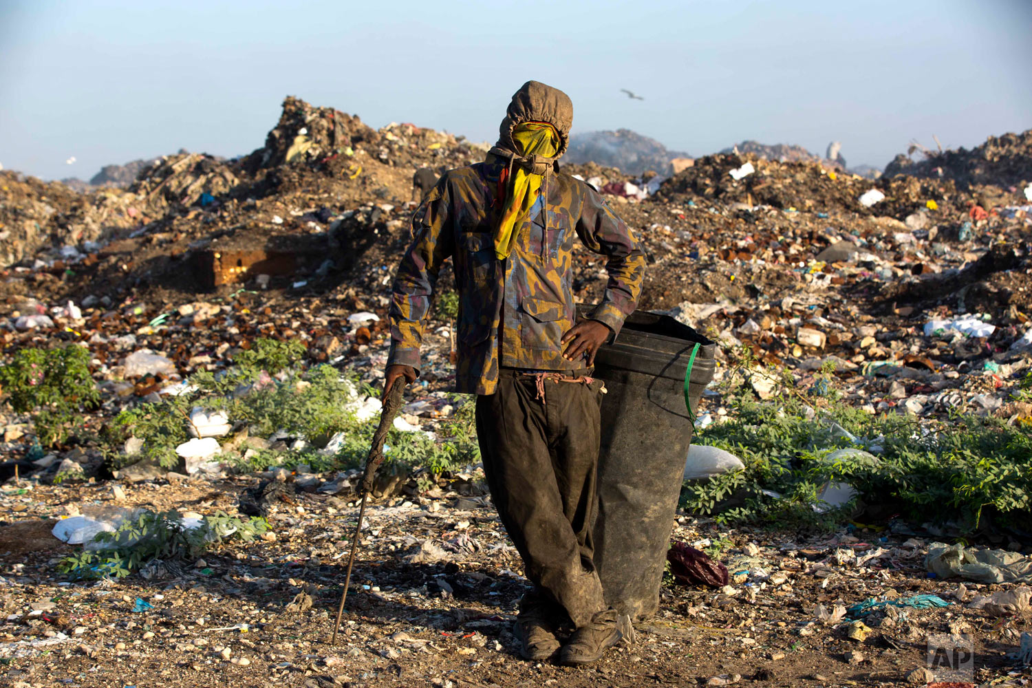 Changlair Aristide pauses for a portrait wearing an old U.N. peacekeeper's jacket he found in the trash. Aug. 24, 2018. (AP Photo/Dieu Nalio Chery)