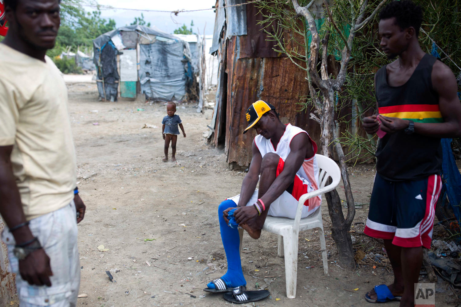 Changlair Aristide, who coaches a soccer team made up mostly of trash scavengers, gets ready to play a game. Aug. 29, 2018. (AP Photo/Dieu Nalio Chery)