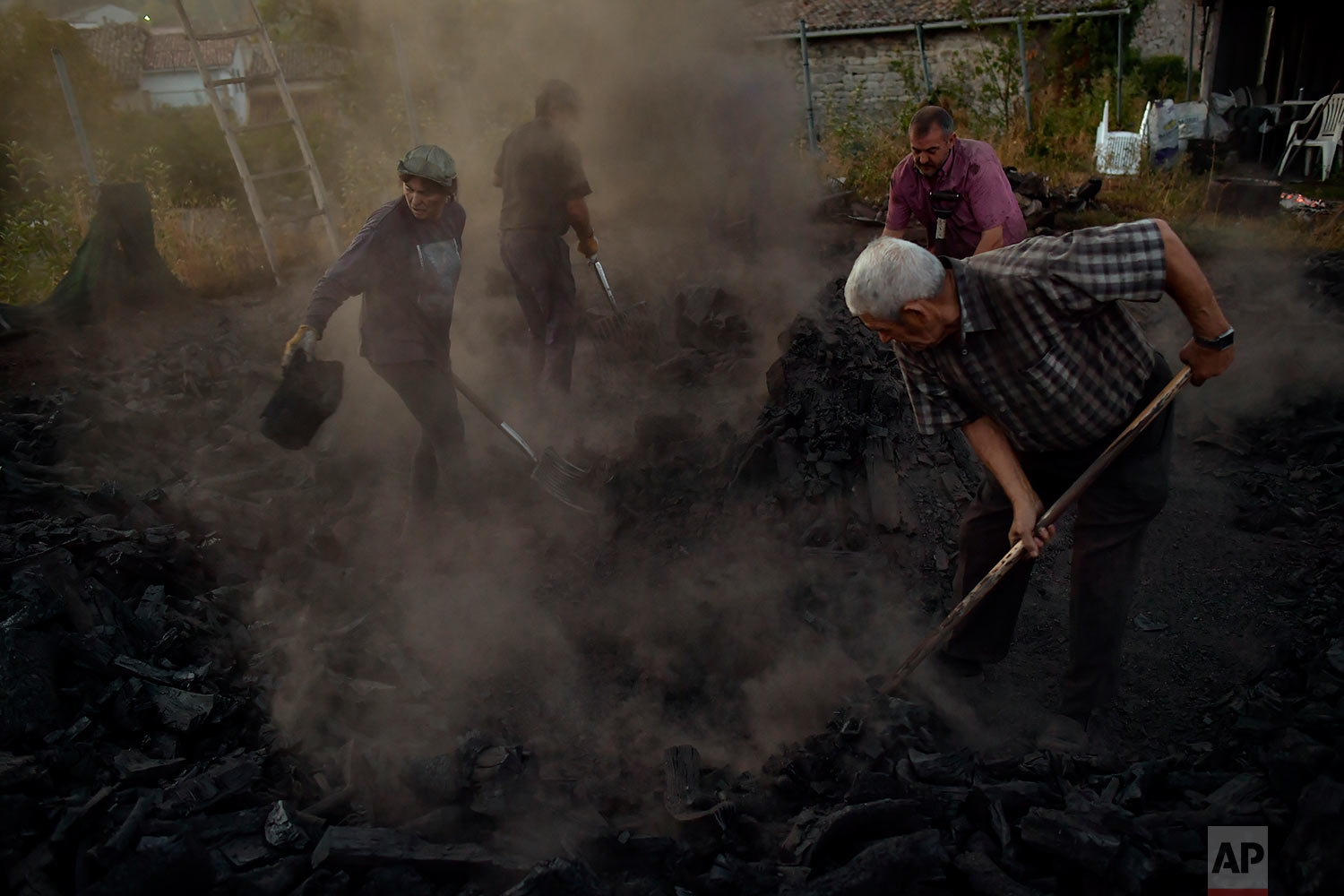 In this Tuesday, Sept.11, 2018 photo, workers extinguish the fire of burning tree trunks, as part of a process to produce traditional charcoal in Viloria, northern Spain. (AP Photo/Alvaro Barrientos)