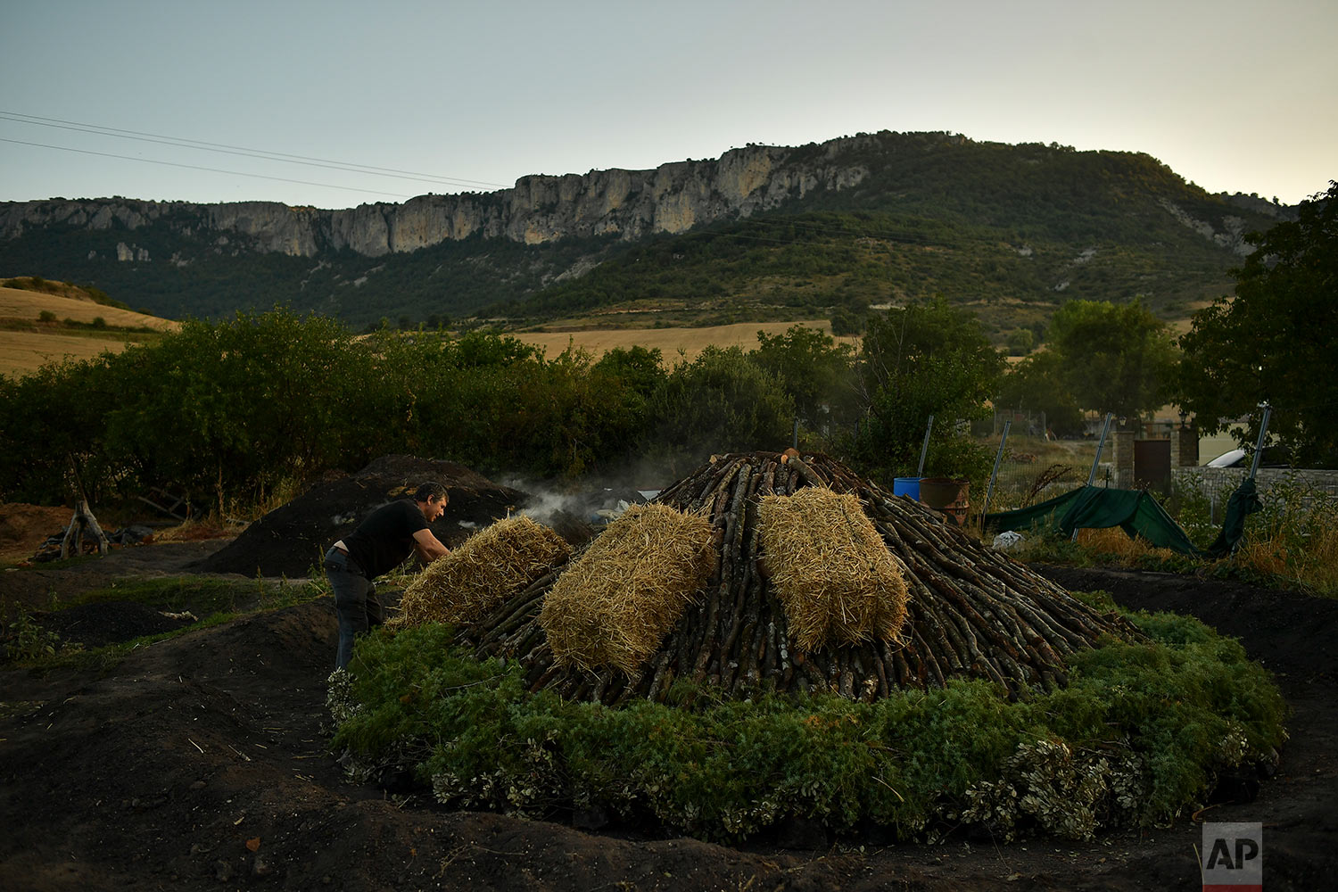 In this Wednesday, Aug. 29, 2018 photo, Miguel Lander, 56, places straw bales on wood piled up as part of the process to produce traditional charcoal, in the town of Viloria, northern Spain. (AP Photo/Alvaro Barrientos)